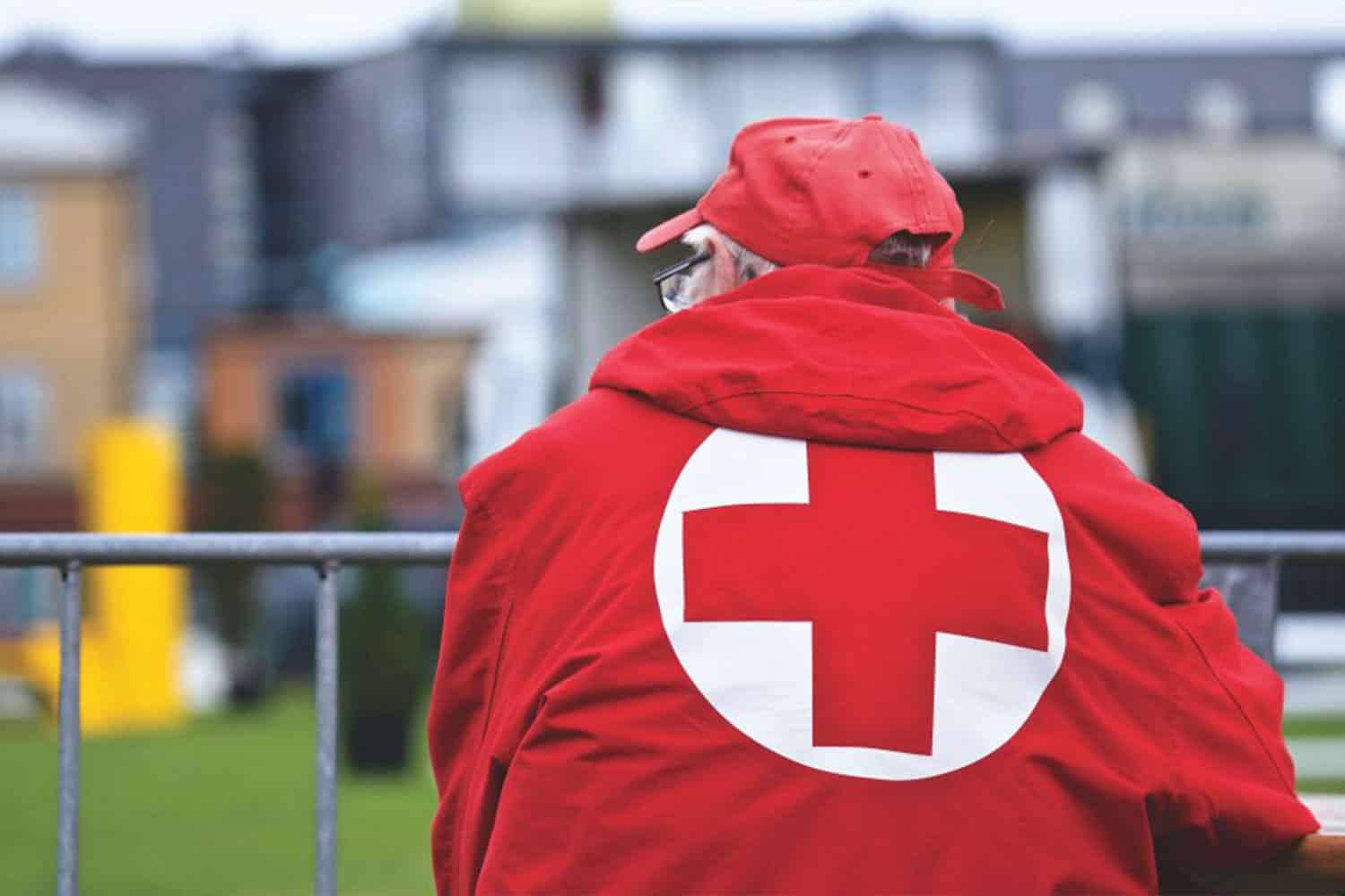 Man with red jacket with red cross on the back